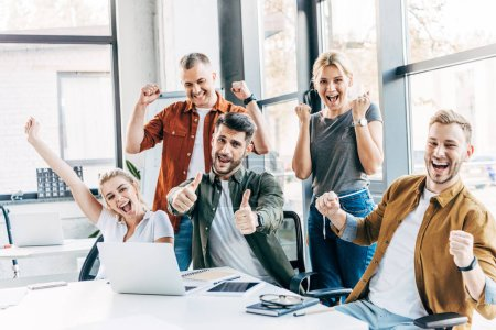 group of happy successful entrepreneurs celebrating victory and showing thumbs up at office and looking at camera