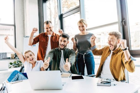 Photo for Group of young successful entrepreneurs celebrating victory and showing thumbs up at office and looking at camera - Royalty Free Image