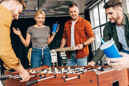 group of happy casual business people playing table football with pizza at office and having fun together