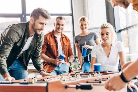 Foto de Toma recortada de empresarios informales expresivos jugando fútbol de mesa en la oficina y divertirse juntos - Imagen libre de derechos