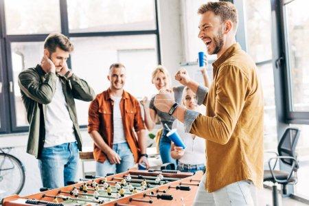 Foto de Empresarios informales expresiva jugando fútbol de mesa en la oficina y divertirse juntos - Imagen libre de derechos