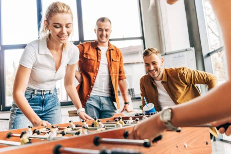 cropped shot of happy casual business people playing table football at office and having fun together