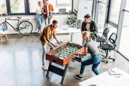 Photo pour Vue angle élevé de jeunes entrepreneurs occasionnels jouer baby-foot au bureau et s'amuser ensemble - image libre de droit
