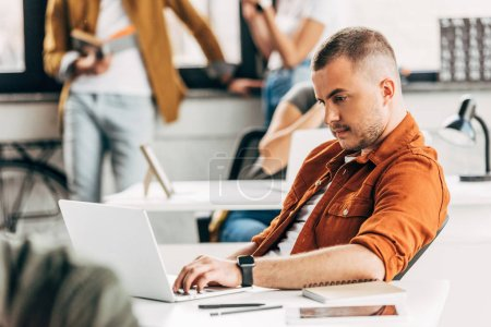 young man working with laptop at open space office with colleagues on background