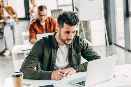 Photo pour Jeune homme réfléchi qui travaille avec un ordinateur portable et un bloc-notes dans un bureau ouvert avec des collègues en arrière-plan - image libre de droit