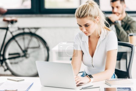 attractive young woman working with laptop at office with colleague on background