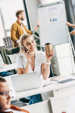 happy young woman talking by phone and drinking coffee at office with colleagues on background