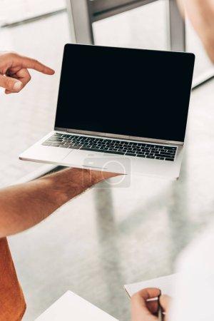 Photo pour Recadrée tir des gens d'affaires pointant sur écran d'ordinateur portable blanc pendant le travail - image libre de droit