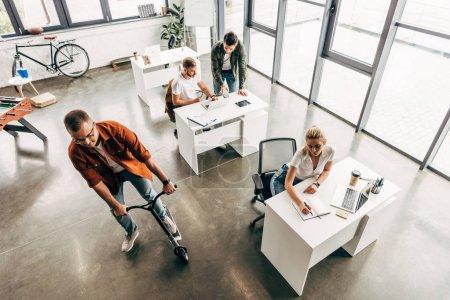 Photo pour Vue grand angle du groupe de jeunes entrepreneurs travaillant sur la démarrage ensemble au bureau ouvert moderne tandis que l'homme équitation scooter - image libre de droit