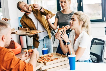 group of young entrepreneurs eating pizza for lunch together while working on startup at office