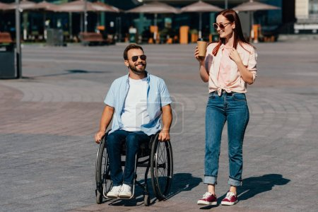 handsome boyfriend in wheelchair and girlfriend with coffee in paper cup having walk on street