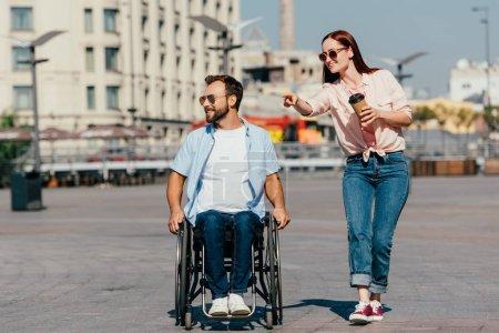 Photo pour Séduisante petite amie pointant sur quelque chose de beau copain en fauteuil roulant sur la rue - image libre de droit