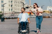 attractive girlfriend pointing on something to handsome boyfriend in wheelchair on street