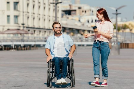 Photo for Smiling handsome boyfriend in wheelchair and girlfriend with coffee to go having walk on street - Royalty Free Image