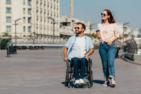 Photo for Handsome boyfriend in wheelchair and girlfriend with coffee in paper cup having walk on street and looking away - Royalty Free Image