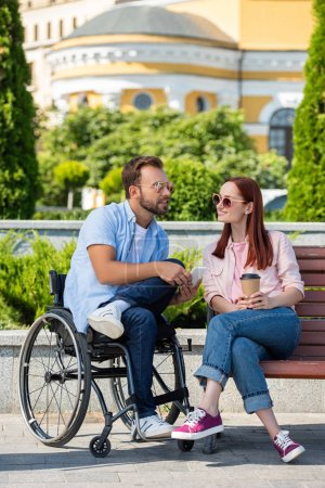 handsome boyfriend in wheelchair with smartphone and girlfriend with coffee to go on street