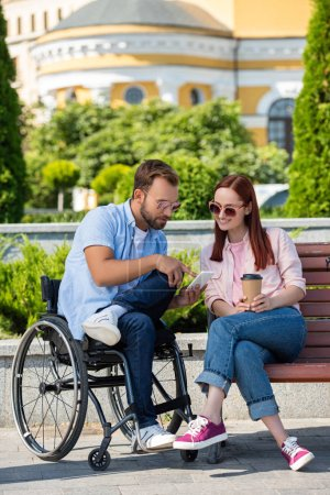 Photo pour Joyeux beau petit ami en fauteuil roulant et petite amie regardant smartphone dans la rue - image libre de droit