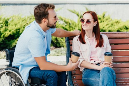 Photo for Handsome boyfriend in wheelchair and girlfriend with coffee to go looking at each other outside - Royalty Free Image