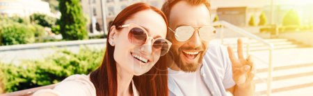 Photo for Panoramic view of happy boyfriend and girlfriend in sunglasses looking at camera in city, man showing peace sign - Royalty Free Image