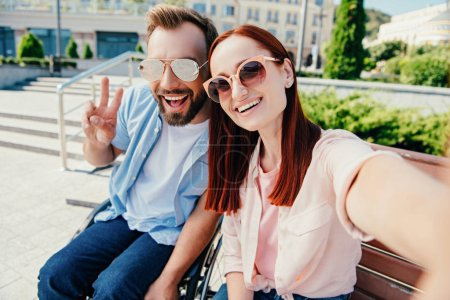 camera point of view of happy boyfriend in wheelchair and attractive girlfriend looking at camera in city, man showing peace sign