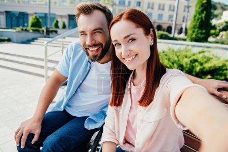 Photo pour Appareil photo point de vue de copain heureux en chaise roulante et superbe copine en regardant la caméra dans la ville - image libre de droit