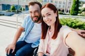 """Постер, картина, фотообои """"точки зрения камеры счастливой бойфренд в инвалидной коляске и красивая подруга смотрит на камеру в городе"""""""