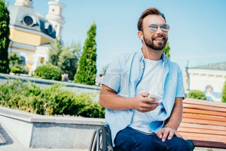 Photo for Smiling handsome man in wheelchair holding smartphone and listening to music on street, looking away - Royalty Free Image