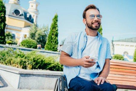 Photo pour Beau homme souriant en fauteuil roulant tenant smartphone et écoutant de la musique dans la rue, détournant les yeux - image libre de droit