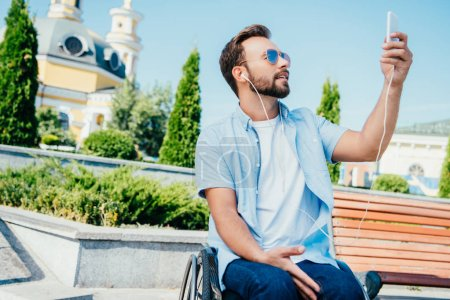 handsome man in wheelchair taking selfie with smartphone and listening to music on street