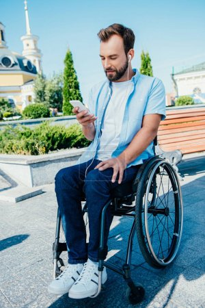 handsome man in wheelchair using smartphone and listening to music on street