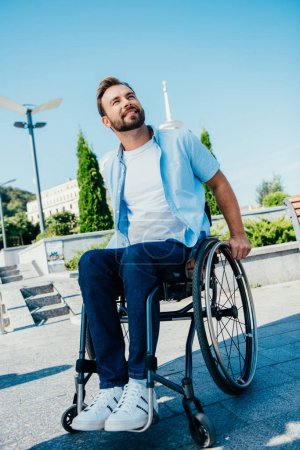 handsome man in wheelchair looking up on street