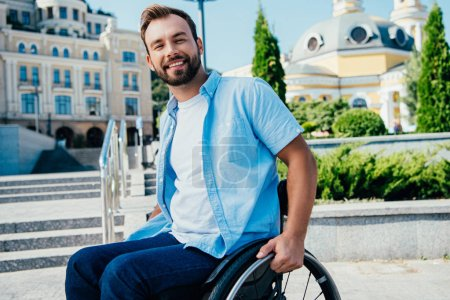 Photo for Cheerful handsome man in wheelchair looking at camera on street - Royalty Free Image