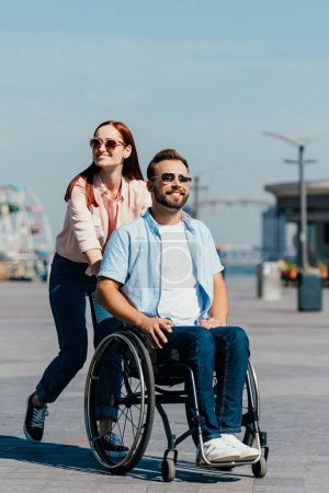 Photo for Attractive girlfriend pushing handsome disabled boyfriend in wheelchair on street - Royalty Free Image