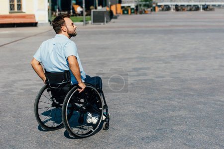 Photo for Side view of handsome man in sunglasses using wheelchair on street - Royalty Free Image