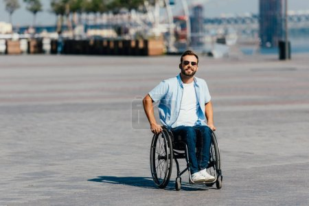 Photo for Smiling handsome man in sunglasses using wheelchair on street - Royalty Free Image