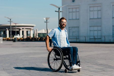 smiling disabled handsome man in sunglasses using wheelchair on street