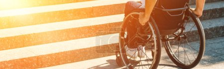 cropped image of disabled man using wheelchair on street and stopping near stairs without ramp