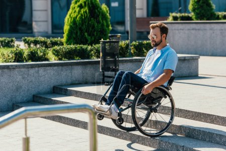 handsome man in sunglasses using wheelchair on stairs without ramp