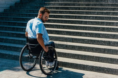 Photo for Handsome disabled man using wheelchair on street and stopping near stairs without ramp - Royalty Free Image