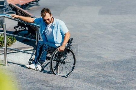 Photo pour Bel homme en lunettes de soleil en fauteuil roulant dans les escaliers sans rampe - image libre de droit