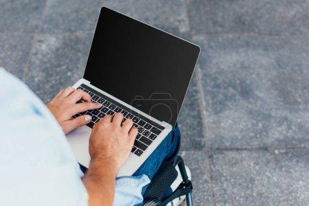Photo pour Image recadrée de l'homme en fauteuil roulant à l'aide d'un ordinateur portable avec écran blanc sur la rue - image libre de droit