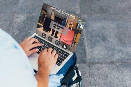 Photo pour Image recadrée de l'homme en fauteuil roulant à l'aide de portable avec le site de réservation en ligne sur la rue - image libre de droit