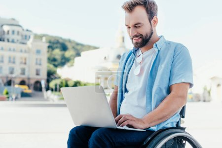 Photo for Cheerful handsome man in wheelchair using laptop on street - Royalty Free Image