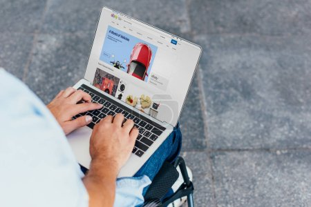 Photo for Cropped image of man in wheelchair using laptop shopping online with ebay website on street - Royalty Free Image