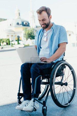 handsome man in wheelchair using laptop on street