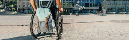 Photo for Cropped panoramic view of man using wheelchair with bag on street - Royalty Free Image