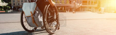 Photo for Cropped panoramic view of man using wheelchair with bag on street with sunlight - Royalty Free Image
