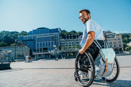 Photo pour Sourire bel homme dans les lunettes de soleil en fauteuil roulant dans la rue et en regardant la caméra - image libre de droit