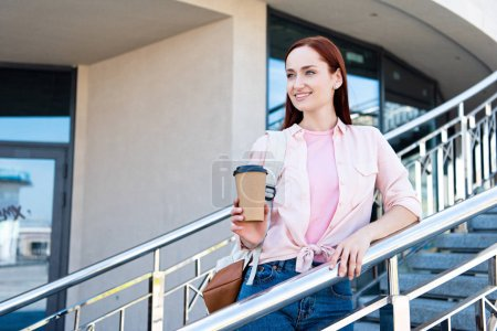 Photo for Attractive redhair woman in pink shirt looking away, leaning on railing and holding disposable coffee cup - Royalty Free Image