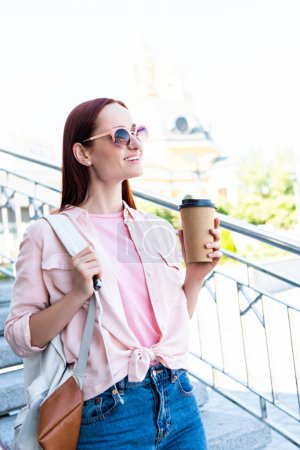 Photo for Smiling attractive redhair woman in pink shirt holding coffee in paper cup and looking away - Royalty Free Image